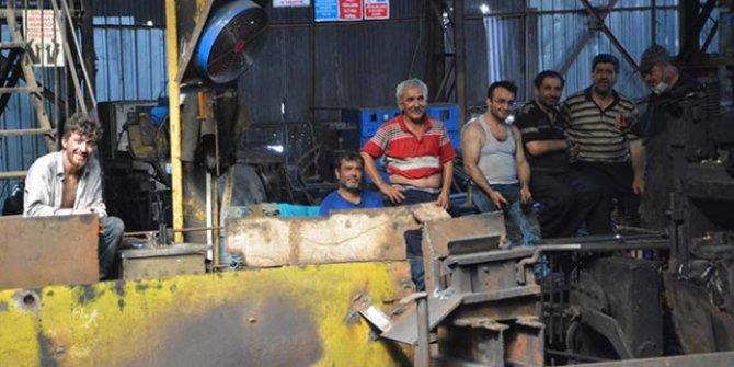Demir işçileri birbirlerine su tutarak serinliyor