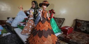 Filistinli Hena oyuncak bebekleri renkli kartonlarla giydiriyor